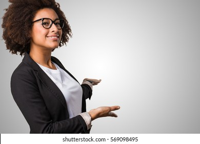 business black woman doing welcome gesture on a grey background