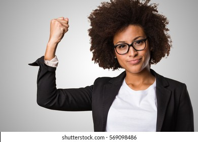 business black woman doing winner gesture on a grey background
