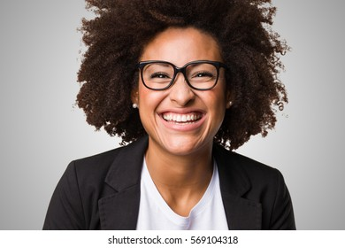 business black woman feeling happy on a grey background
