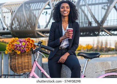 Business black woman with vintage bicycle by the river drinking coffe