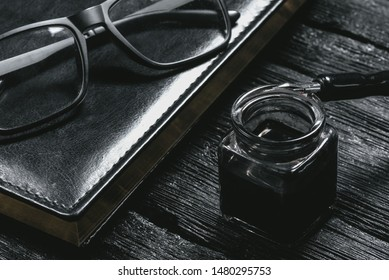 Business book, inkwell with a quill pen and eye glasses on black wooden table. Business concept background.