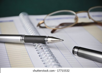 Business Books, Charts, Expenses, Bookkeeping, Pen w/ Glasses on top of spiral bound monthly accounting income and expense reports.