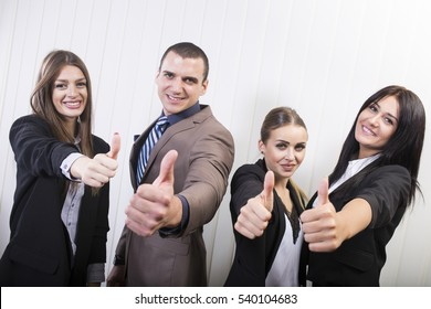 Business is booming. Successful young business team giving thumbs up. Beautiful business women with a business man.