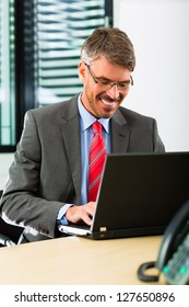 Business - Boss in his office checking mails on laptop computer