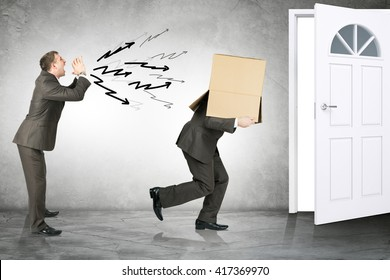 Business boss shouting to employee with box on his head and running away