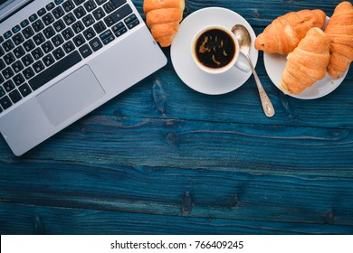 Business breakfast, coffee and croissants, on a wooden surface. Top view. Free space for text.
