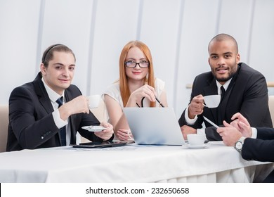 Business breakfast. Confident businessman sitting at a laptop and looking at the camera while drinking coffee. Businessmen sitting at a table at a meeting in the office.