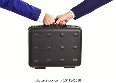 Business bribe concept. Handover of case in hands of business partners, isolated on white background. Male hands in suits hold black briefcase with cash. Male hands carry briefcase for exchange.