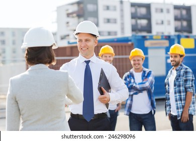 business, building, teamwork, gesture and people concept - group of smiling builders in hardhats with clipboard greeting each other outdoors