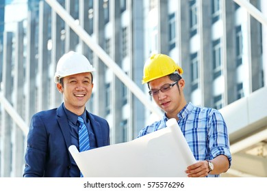 business, building, teamwork and people concept. Engineer is smiling with his project while architect looking at blueprint .Construction project with office buildings