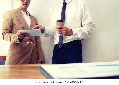 business businessman and woman stand in meeting analyses, on the table have chart graphy marketing plan in business project. sepia tone