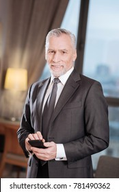 Business call.  Positive enthusiastic senior man calling his employees  while  holding phone  and looking at the camera