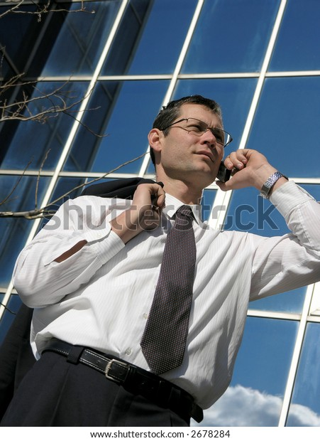 Business call. Young businessman talking to the cell phone in front of an office  .