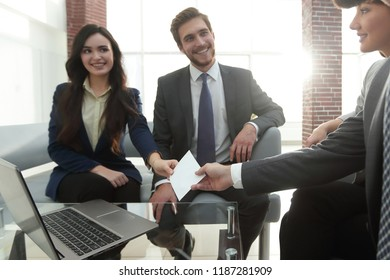Business card being passed over between a male and female busine