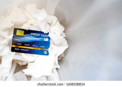 Business card concept, blue credit card on tissue paper in bin, comercial electronic card for pay shopping in world, cheap and no buying throw in bin for trash, white paper and plastic bag garbage