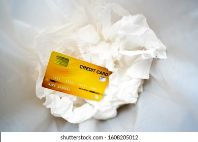 Business card concept, golden credit card on tissue paper in bin, comercial electronic card for pay shopping in world, cheap and no buying throw in bin for trash, white paper and plastic bag garbage