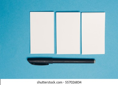 business card on a blue background and a pen