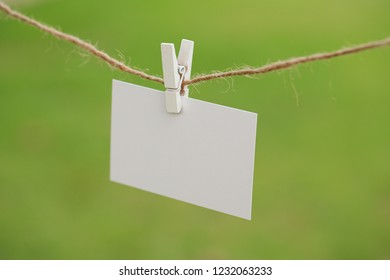 a business card on a clothespin, a card on a rope, a piece of paper on a clothespin