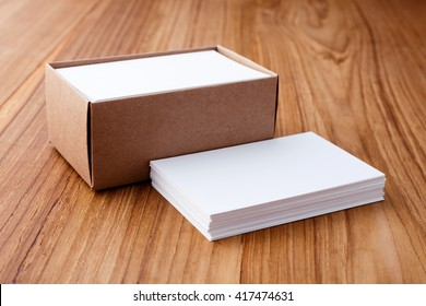 Business card stack blank mockup with kraft box on wood desk