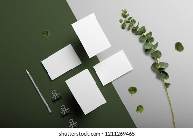 Business cards blank mockup and stationery set, with floral elements, top view, on white and green background.