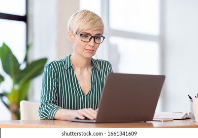 Business Career. Mature Office Manager Lady Working On Laptop Computer Sitting At Workplace Indoor. Selective Focus