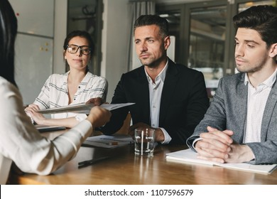 Business, career and placement concept - board of directors sitting at table in office and examining resume of female worker during meeting