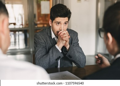 Business, career and placement concept - caucasian uptight male applicant worrying and putting fists together during job interview in office with board of directors