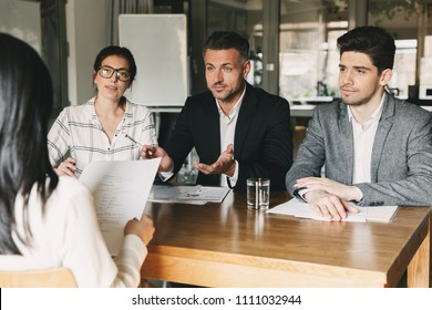 Business, career and placement concept - three executive directors or head managers sitting at table in office and interviewing woman with documents or resume in hands