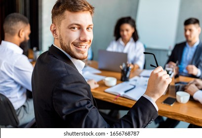 Business Career. Young Businessman At Corporate Meeting With Colleagues Smiling To Camera Sitting In Modern Office.