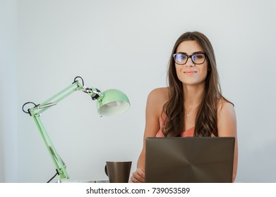 Business casual woman sitting at desk working on laptop computer, smiling and looking at camera.
