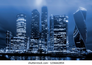 The business center and skyscrapers of big city at night in the fog.