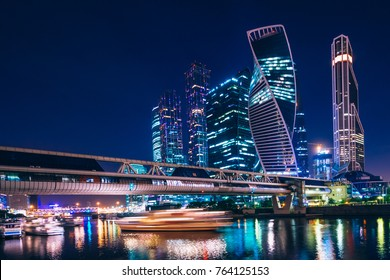 Business center with skyscrapers of Moscow-city at night under the blue sky and with reflections of the illumination on the water. Cityscape