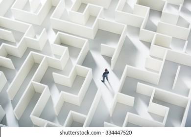 Desafio de negócios. Um homem de negócios navegando por um labirinto. Vista superior