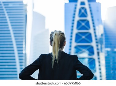Business challenge. Confident businesswoman overlooking the city center high-rises.