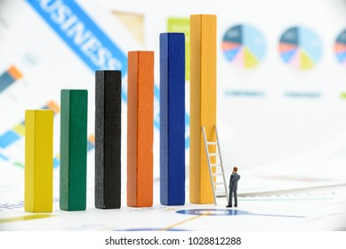 Business challenge or market entry barrier concept : Businessman stands and thinks near a white ladder that leans against wood bars, depicts the level of toughness that new entrepreneur will encounter