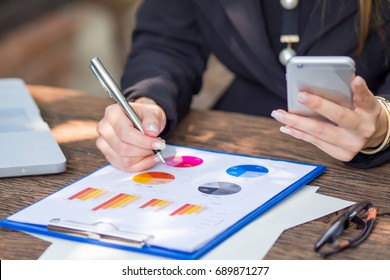 Business chart analysis, business women is looking to sales chart and analysis for the result on wooden table and see her mobile phone.