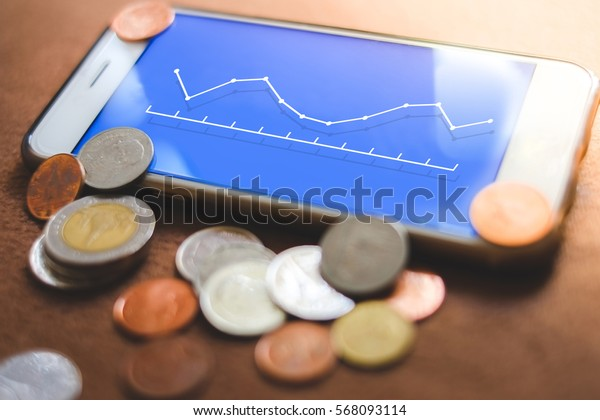 the business chart on a smartphone, representing business growth (Line graph) and a lot of coins around.