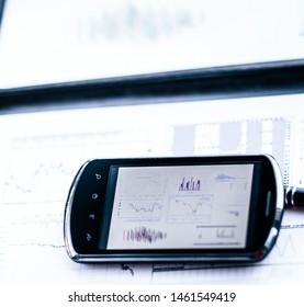 Business chart with a smart phone and a pen on a desk in the off