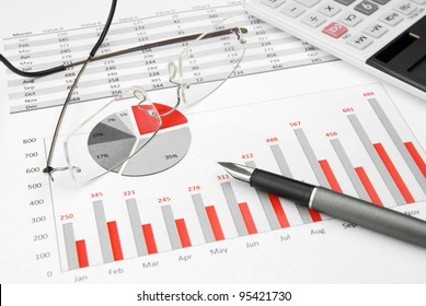 Business Charts Black and Red with calculator, glasses and pen