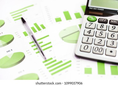 Business charts and graphs, calculator, pen