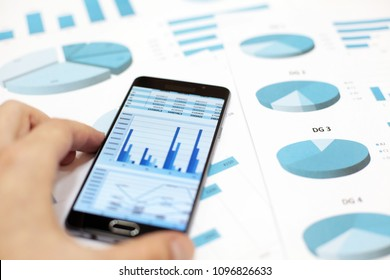 Business charts and graphs on paper and in smartphone
