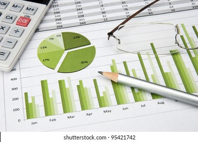 Business Charts Green with calculator, glasses and pen