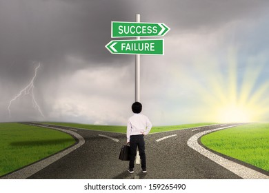 Business child is standing on the road with a sign of success or failure