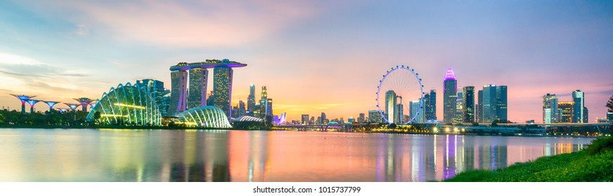 Business city district of Singapore Skyline with modern tower building skyscrapers lighting on twilight colorful of sky with cloud and reflection in water river. Popular travel destination.