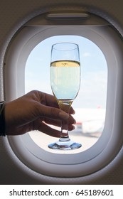 Business class in a passenger airplane. A glass of champagne in hand on the background of the aircraft window.