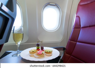 Business class in a passenger plane. On a folding table, a glass of champagne, cakes with cream, canape.