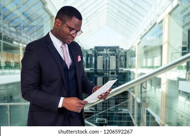 Business coach at the meeting conference.Confident african speaker holding paper documents with graphs, black businessman in suit at seminar inside the business center office