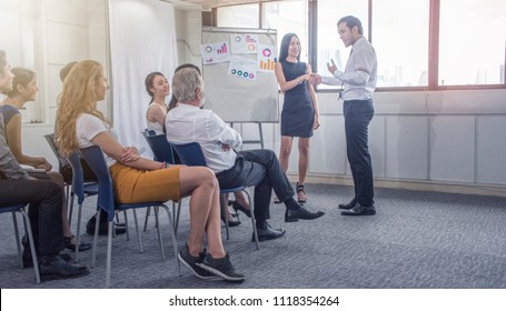 Business coach. Presenter  introducing new friend and co worker ,workshop  .Group of people sitting at the chairs in meeting room.