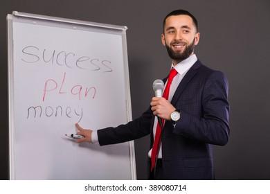 Business coach writes on the blackboard marker