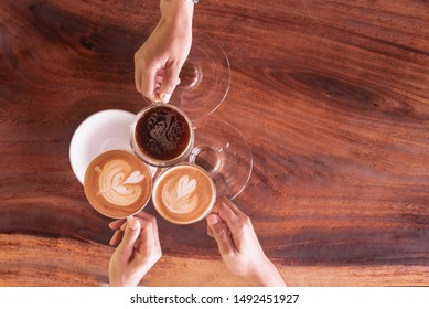 Business coffee break after success discussion cheers the cup of coffee.Friendship meeting in weekend at coffee shop.People hand holding coffee cup and cheers for agreement after negotiation.